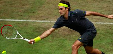 Federer of Switzerland returns a ball to Mayer of Germany at the Halle Open ATP tennis tournament in Halle